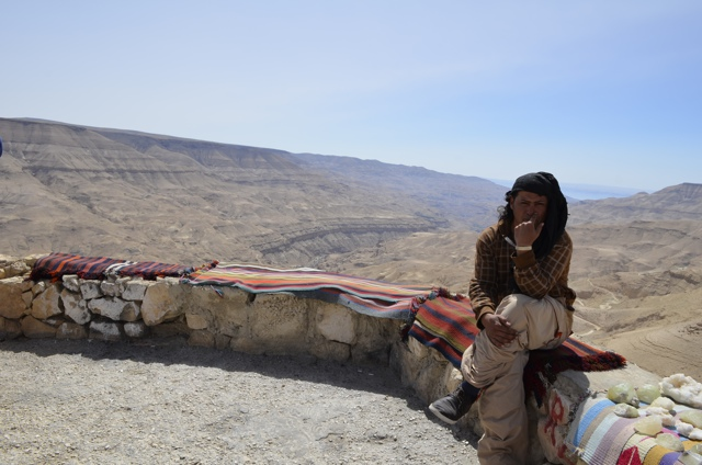 A man selling souviners overlooking the Mujib Dam Valley
