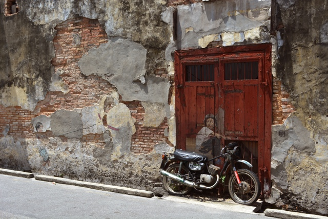 boy on his old motor cycle boy and his pet dinosaur - The Street Art of George Town, Penang, Malaysia