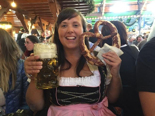 Cailin looking the part at Oktoberfest with a real traditional dirndle dress, liter beer and pretzel - Where to buy a dirndl dress and lederhosen pants for Oktoberfest in Munich