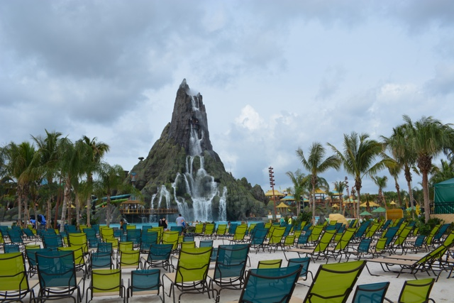 lots of open lounge chairs on waturi beach in front of the krakatau volcano - Ultimate Guide to Relaxing at Universal's Volcano Bay