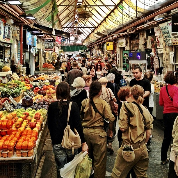 locals, military soliders and tourists explore the MachneYehuda market in Jerusalem, Israel