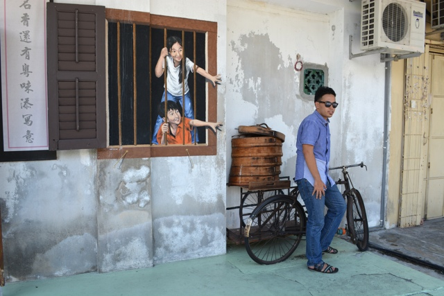 brother and sister behind bars dim dum delivery bicycle - The Street Art of George Town, Penang, Malaysia