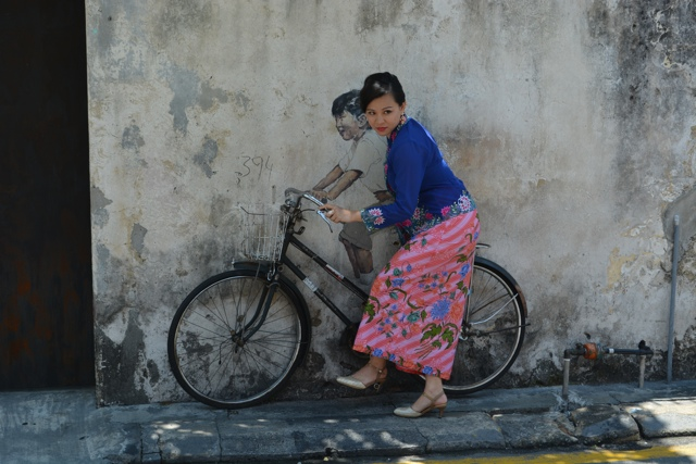a model poses next to the kids on a bicycle 3D painting street art in Georgetown by Ernest Zacharevic - The Armenian Street Heritage Hotel in Georgetown, Penang, Malaysia