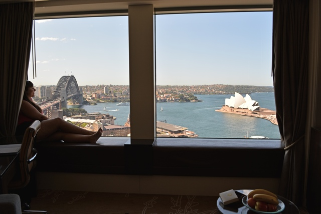 Cailin O'Neil with a stunning view of the Sydney Harbour, bridge and Opera House from the Shangri-la in Sydney, Australia - Five Places I Would Travel to with an Unlimited Budget