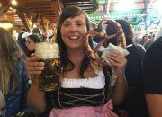 Cailin looking the part at Oktoberfest with a real traditional dirndle dress, liter beer and pretzel - Where to buy a dirndl dress and lederhosen pants for Oktoberfest