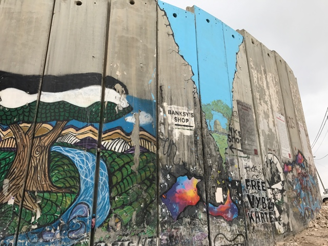 walking outside Banksy's Walled Off Hotel you are right next to the graffiti colored israel west bank barrier wall - How to Get to Banksy's Walled Off Hotel