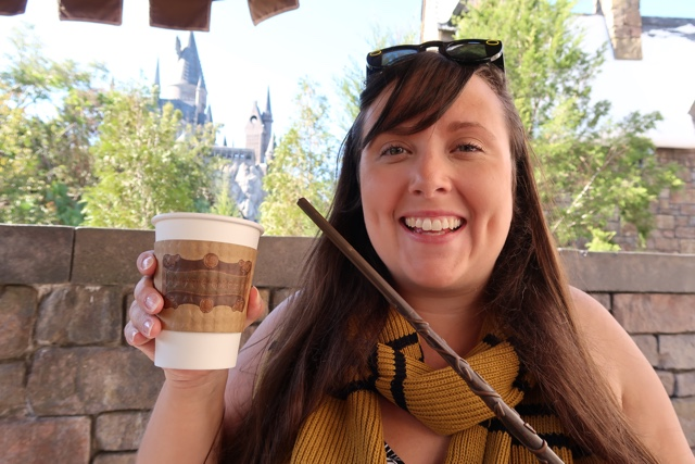 cailin enjoying hot butterbeer with hufflepuff scarf and hermione wand - Best Tips for Celebrating the Holidays at Universal Orlando