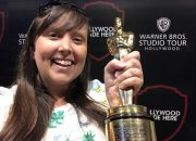 Cailin holding an award winning oscar from the academy of arts and sciences at the warner brothers studio tour