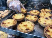 A baker places pastel de nata pastries in the shop window