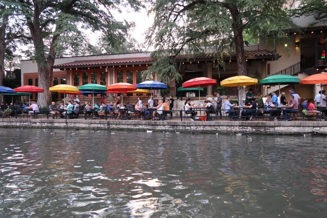 people dine along the san antonio riverwalk under the colorful rainbow umbrellas of the case rio restaurant - things to do in san antonio today