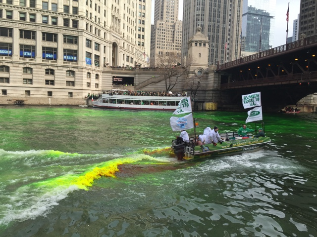 plumbers dumping dye into the Chicago river - guide to st patricks day in chicago