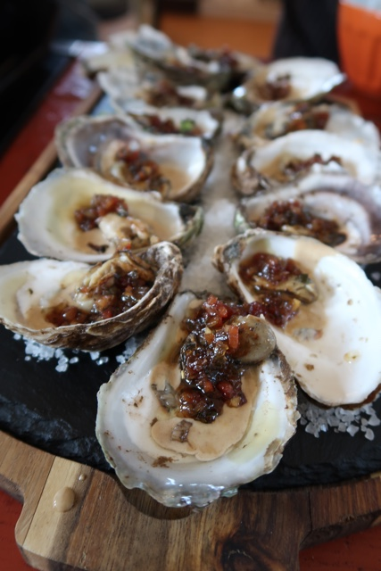 grilled oysters in a black garlic cream sauce with bacon jam